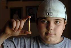Bradley Geslak holds an empty bullet casing like the one that got him suspended